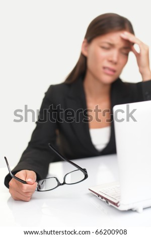 Headache and Stress at work. Young professional woman stressed and tired with headache sitting at office desk. Shallow depth of field, focus on glasses. - stock photo