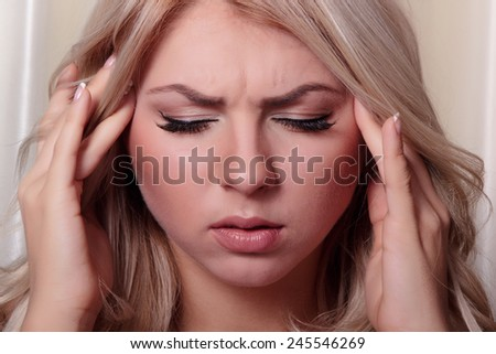 Headache, migraine and stress. Worried woman upset woman suffering from head pain  - stock photo