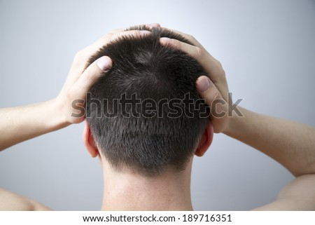 Headache of the man on gray background. Nape young adult man - stock photo