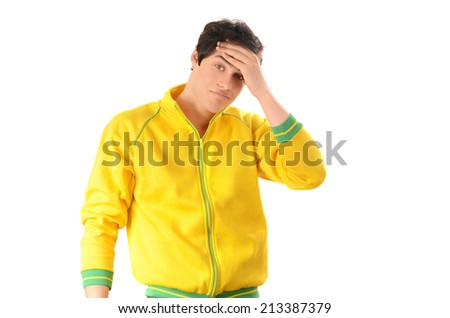 Headache, sadness, stress. Young man dressed with a yellow sports blouse holding his forehead with worry. Isolated on white background. - stock photo