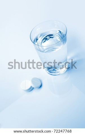 Headache tablets and glass of water.