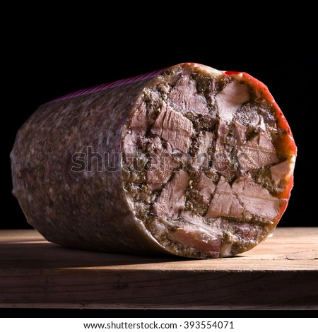 Headcheese served on wood with black background
