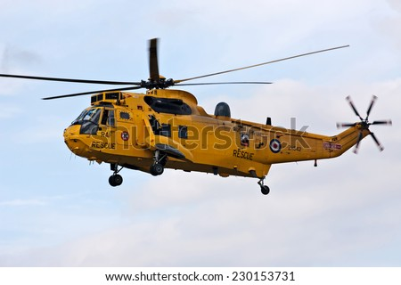 HEADCORN, UK - AUGUST 16: A Sea King helicopter from the Search and Rescue team of the RAF gives a low level display to the public at the Combined Ops show on August 16, 2014 in Headcorn - stock photo