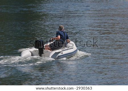 heading back to his yacht in his inflatable zodiac - stock photo