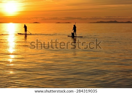 Heading For The Sun Paddle boarders are chasing a beautiful sunset on the Strait of Georgia. - stock photo