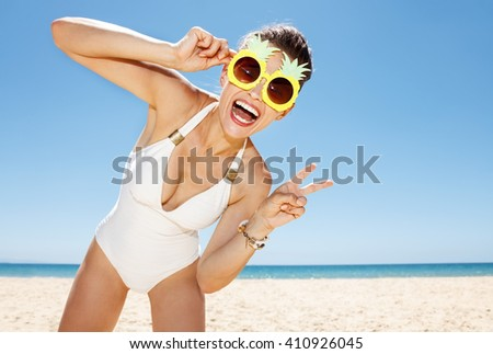 Heading to white sand blue sea paradise. Portrait of smiling woman in white swimsuit and funky pineapple glasses showing victory gesture at sandy beach on a sunny day - stock photo