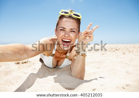 Heading to white sand blue sea paradise. Smiling woman in white swimsuit and funky glasses showing victory gesture and taking selfies while laying on sandy beach on a sunny day - stock photo