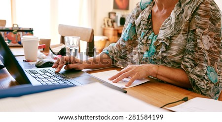 Headless cropped image of a mature business woman busy working on her laptop computer in her home office - stock photo