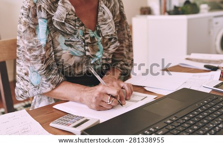 Headless cropped image of an older business woman busy working out her finances at her desk in her home office - stock photo