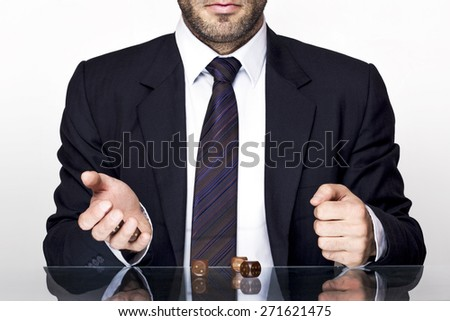 Headless man in suit gambling with wooden dices on a glass table - stock photo