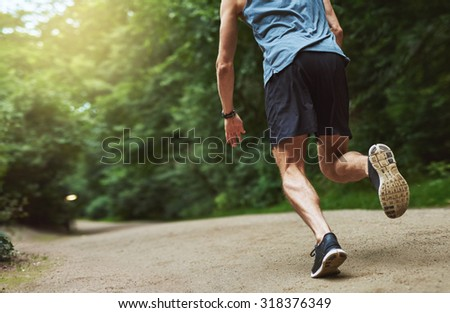 Headless Rear View Shot of an Athletic Young Man Running at the Park Early in the Morning. - stock photo