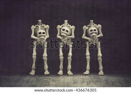 Headless skeletons holding their own head with black background grungy textured - stock photo