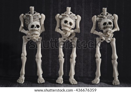 Headless skeletons holding their own heads with black background - stock photo
