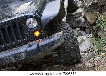 Headlight and grille on a four-wheel drive vehicle traveling over rocks. - stock photo