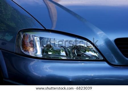 Headlights of a shiny blue car - stock photo