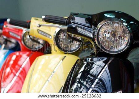 Headlights of three scooters, black, yellow and red. Shallow depth of field with the first scooter in focus. - stock photo