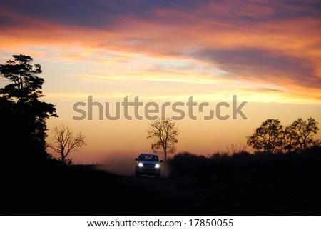 Headlights on and throwing dust in the air, a car races along a dirt road in a Brazilian rainforest - stock photo