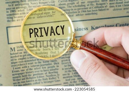 Headline of newspaper through magnifier. Headline of newspaper through magnifying glass, with Privacy word  - stock photo