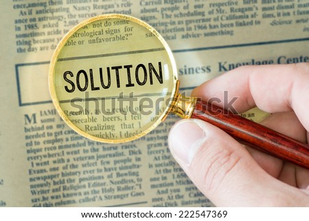 Headline of newspaper through magnifying glass, with Solution word - stock photo