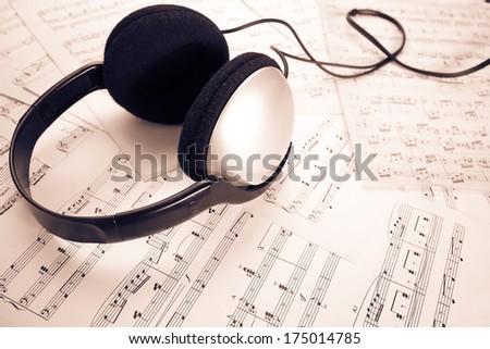 headphone on music sheet sepia processed - stock photo