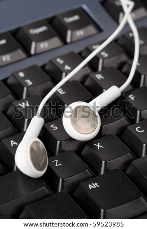 Headphones and black keyboard, concept of digital music - stock photo