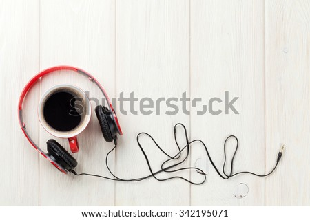 Headphones and coffee cup on wooden desk table. Music concept. Top view with copy space - stock photo