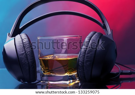 headphones and glass of whiskey against two colored background - stock photo