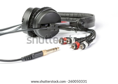 Headphones and golden jack plug isolated on white ground - stock photo