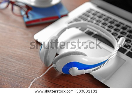 Headphones and laptop on wooden table closeup