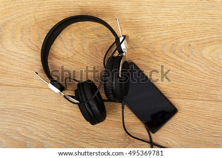 Headphones and mobile phone on a wooden surface