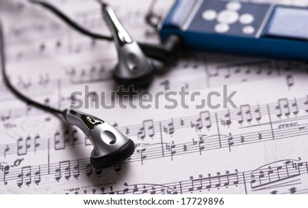 Headphones and MP3 player with minimum Dof on a music sheet. - stock photo