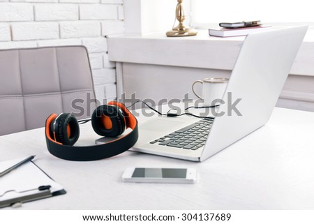 Headphones and other devices on wooden desktop in office - stock photo