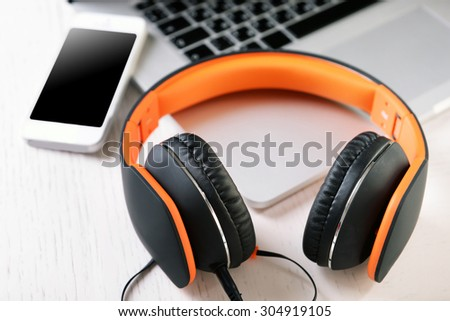 Headphones and other devices on worktop, closeup - stock photo