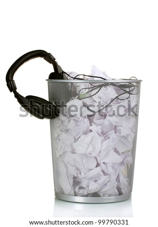 headphones and paper in metal trash bin isolated on white - stock photo