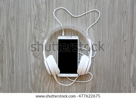 headphones and smartphone on wooden background