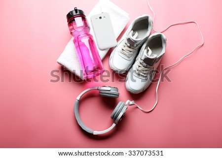 Headphones and sport equipment on pink background - stock photo