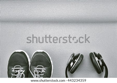 Headphones and sport shoes on yoga mat background, Fitness and exercise equipment, Entertainment workout concept. (Black & White) - stock photo