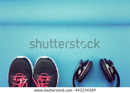 Headphones and sport shoes on yoga mat background, Fitness and exercise equipment, Entertainment workout concept. (Vintage Style Color) - stock photo