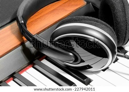 Headphones are on the piano keys closeup - stock photo