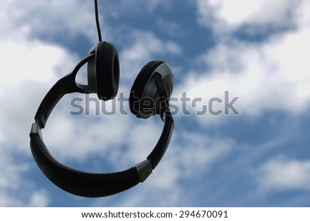 headphones in nature against the sky