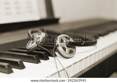 Headphones lying on the piano keys closeup - stock photo