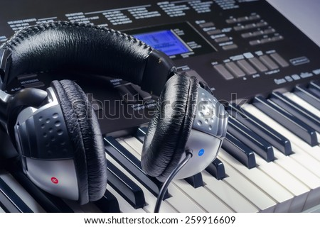 Headphones lying on top of a synthesizer buttons - stock photo