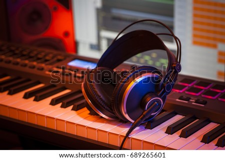 Headphones on a MIDI keyboard in a home studio with a computer screen and speaker in the background. Selective focus and orange coloured lighting.
