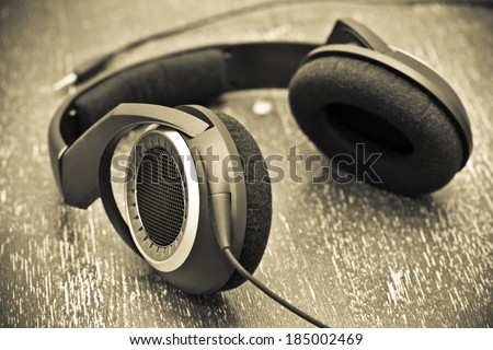 Headphones on a wooden table in vintage style - stock photo
