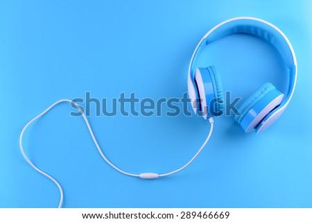 Headphones on blue background - stock photo