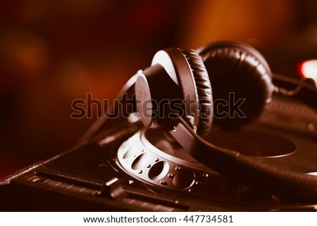 Headphones on CD music disc player for DJ. Top class audio equipment for studio,event,concert. Widely used by professional disc jockey. Macro, close up - stock photo