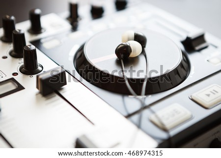 Headphones on DJ midi controller turntable. Close up on sound equipment. Knobs, fader, jog wheel