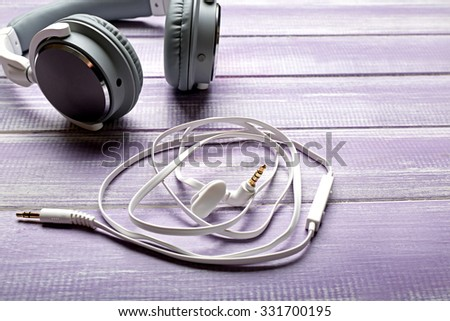 Headphones on wooden lilac background