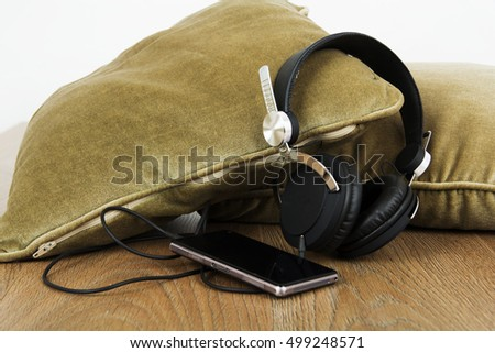 Headphones resting on cushions on a wooden surface