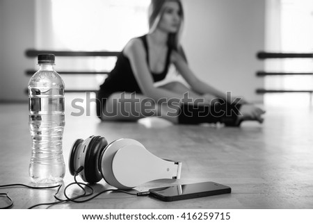 headphones, water in bottle  and smartpone on background of young girl dancer warming up in dance class. Black and White. Focus on headphones